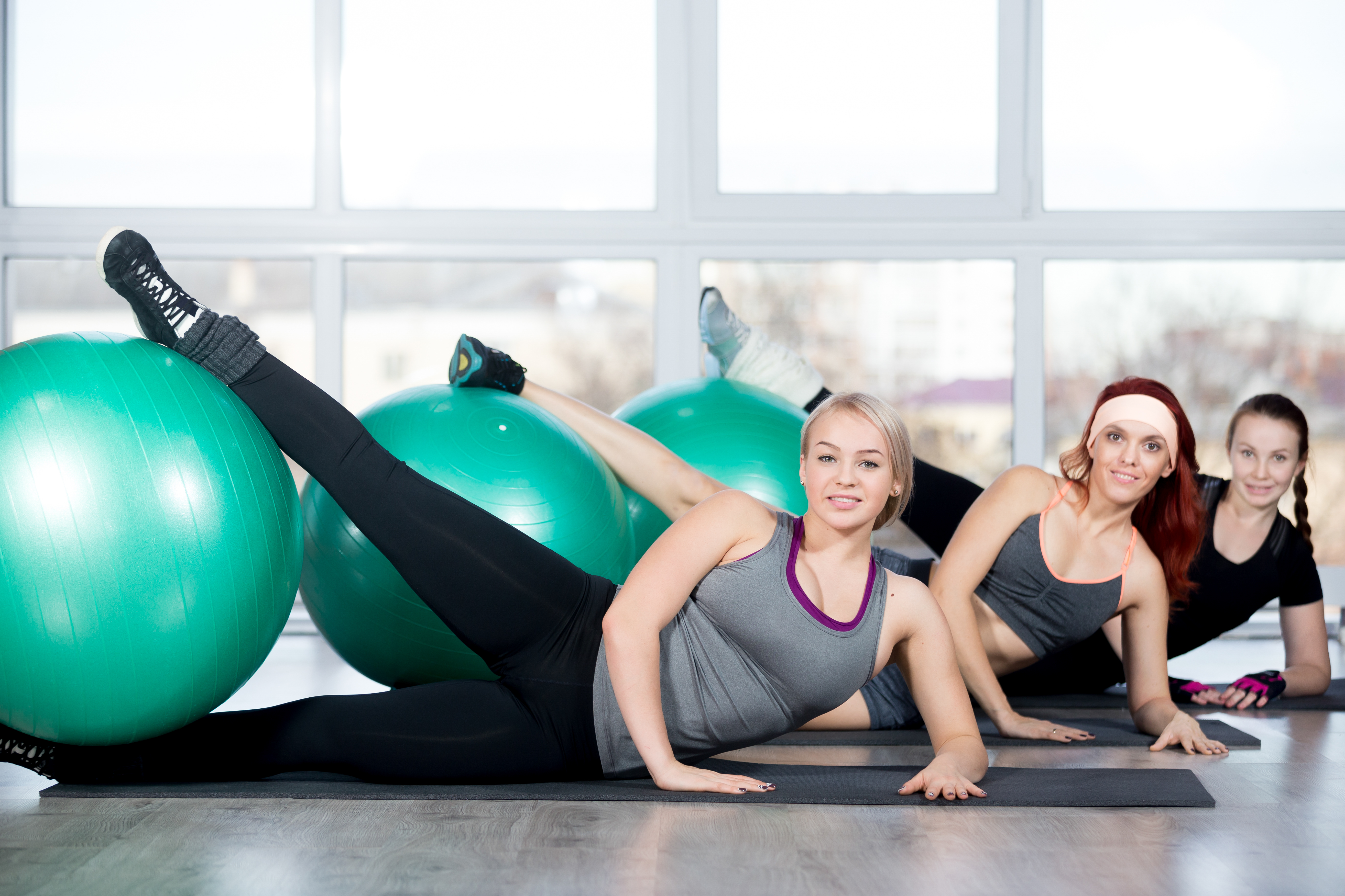 Fitness practice, group of three cheerful beautiful fit young females working out in sports club, doing exercise for hips on green Swiss balls in class, full length